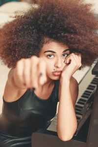 woman leaning on piano while raising right hand forward